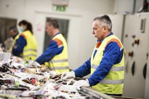 Senior worker sorting papers on factory assembly line for recycling at recycling plant.